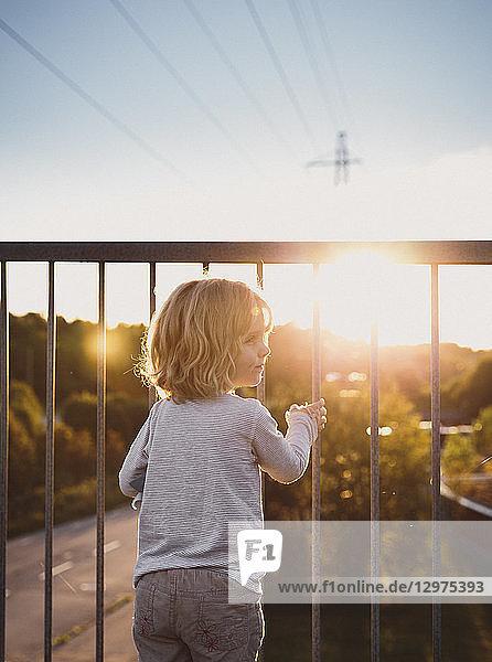 Girl standing on a balcony at sunset in Skarpnack  Sweden