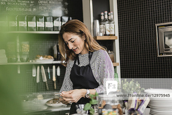 Barista holding smart phone at cafe counter