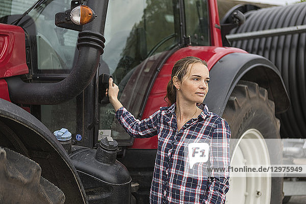 Agricultural worker standing next to a tractor in field