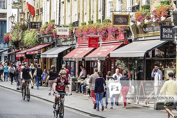 United Kingdom Great Britain England  London  Covent Garden Wellington Street  shopping dining entertainment district  restaurants  sidewalk cafe  awnings  flower planters  adjoining businesses  man  woman  pedestrians  cyclist  bicycles  Cicchetti  Bella Italia  Onthebab  Cafe Rouge