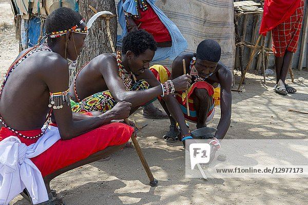 Young Samburu warriors demonstrating how to start a fire with sticks in a Samburu village near Samburu National Reserve in Kenya.