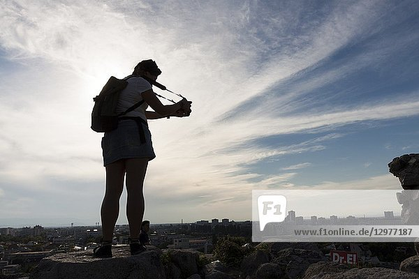 Young woman photographs the panorama at sunset. Plovdiv  Bulgaria.