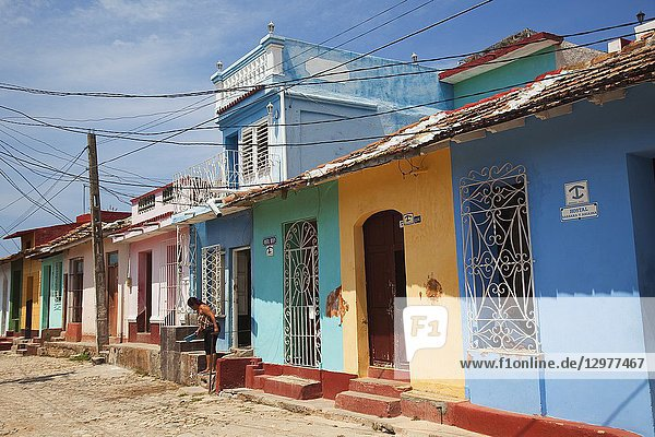 Local woman in front of the colorful colonial houses at the historic center  Trinidad  Sancti Spiritu Province  Cuba  Central America