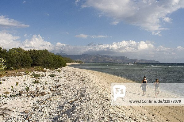 Scenic Landscape. Sunset at Gili Meno Island. Lombok  Indonesia. Some tourists walking along the beach in the western part of the island  the most untouched by tourists. Gili Meno.