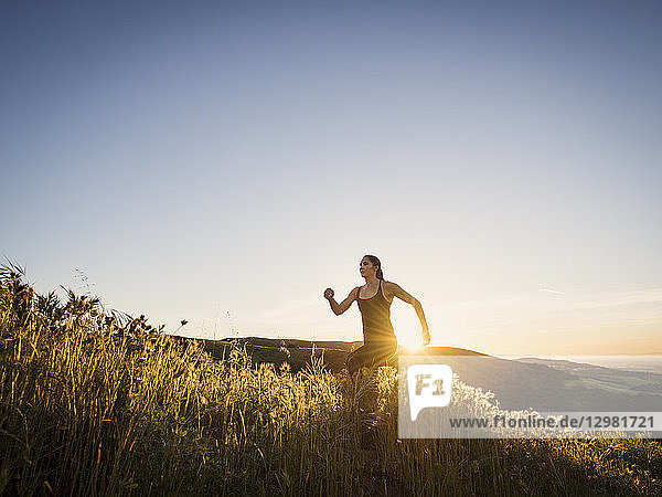 Mid adult woman jogging at sunset