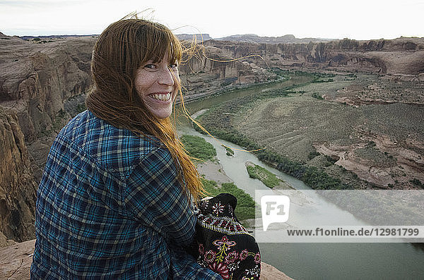 Smiling woman sitting at the Grand Canyon