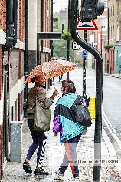 England  London  South Bank Southwark  Union Street  sprinkling  light rain  holding umbrella  Black  woman  covering  sharing  friends