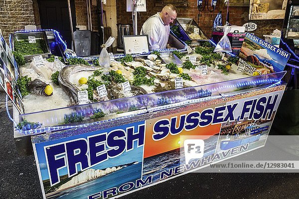 England  London  South Bank Southwark  Borough Market  vendors stalls  Fresh Sussex Fish  fishmonger  ice bin  man  display sale  seafood