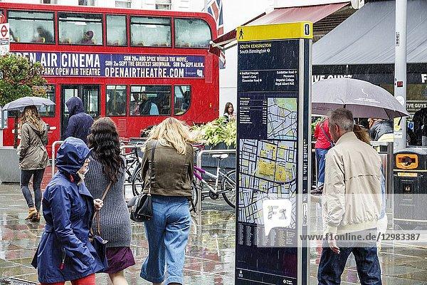 United Kingdom Great Britain England  London  South Kensington  weather  rain raining  wet pavement  umbrellas  man  woman  pedestrian  Legible London Wayfaring sign  on street pedestrian map  neighborhood directions  red double-decker bus