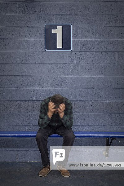A man  his head in his hands  sitting on a bench underneath the number 1.