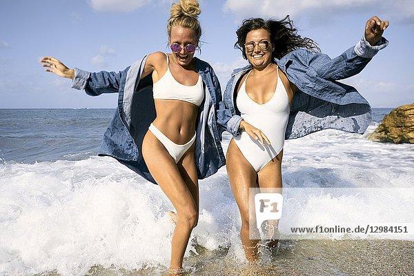 Two women in sea water at beach  Chersonissos  Crete  Greece.