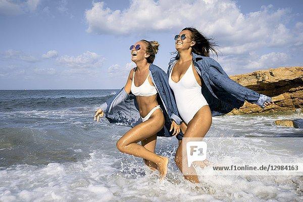 Two women running in sea water at beach  Chersonissos  Crete  Greece.