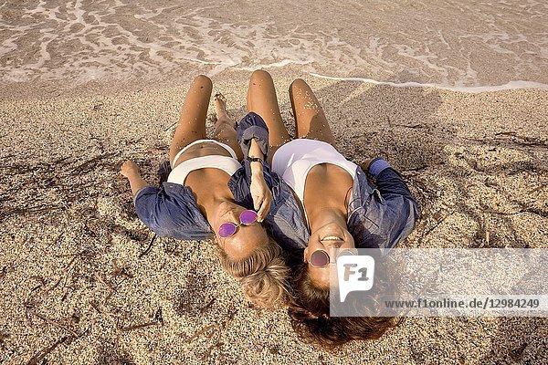 Two women lying in sand on beach  Chersonissos  Crete  Greece.