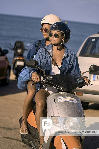 Two women driving scooter  Chersonissos  Crete  Greece.