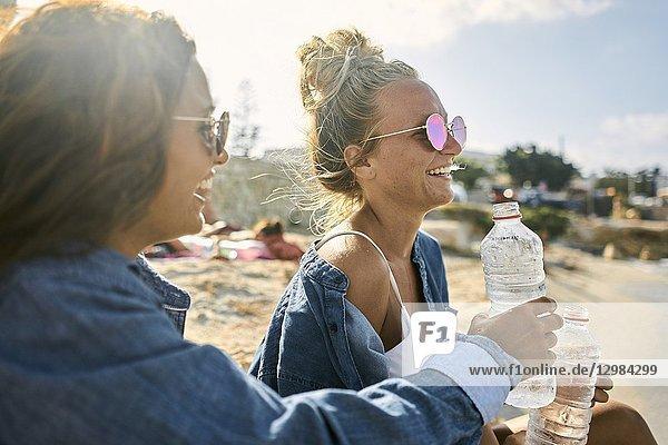 Two women sitting at beach  Chersonissos  Crete  Greece.