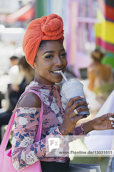 Smiling young woman in headscarf drinking smoothie