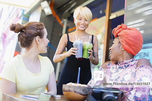 Waitress serving smoothies to women friends at sidewalk cafe