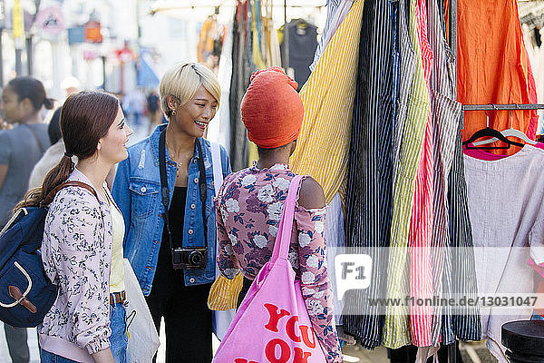 Young women friends shopping on urban sidewalk