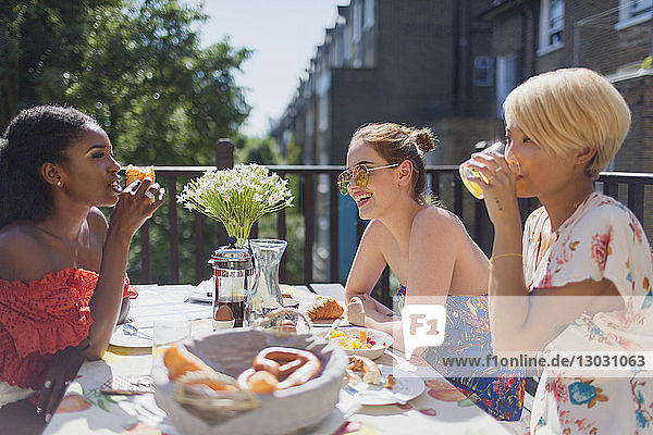 Young women friends enjoying brunch on sunny apartment balcony