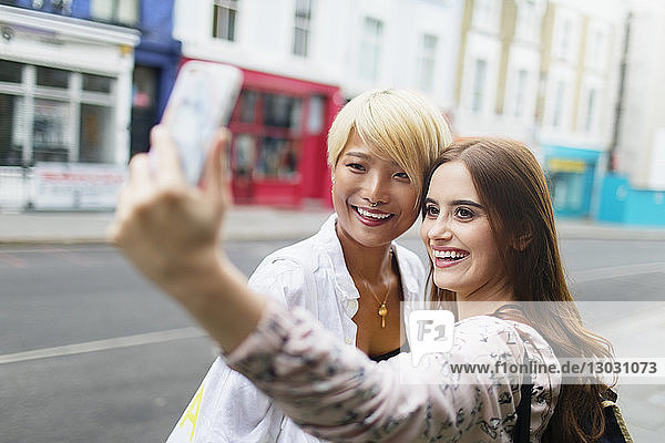 Young women friends taking selfie with smart phone on urban street