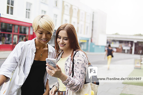Young women friends texting with smart phone on urban street