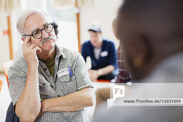 Attentive senior man listening in group therapy