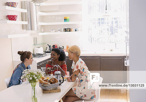 Young women friends enjoying breakfast at dining table