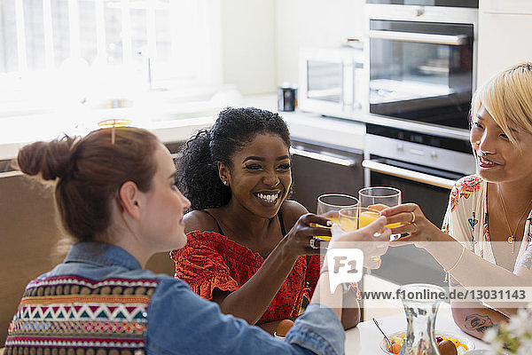 Happy young women friends toasting cocktails in apartment kitchen