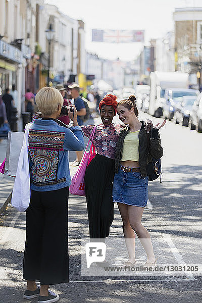 Young women friends posing for photograph on urban street