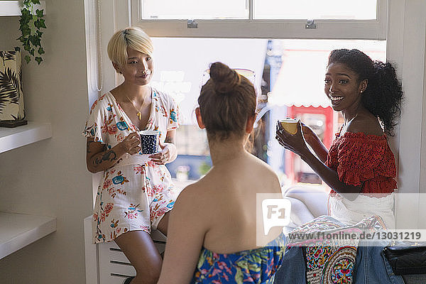 Young women friends drinking coffee and talking in apartment window