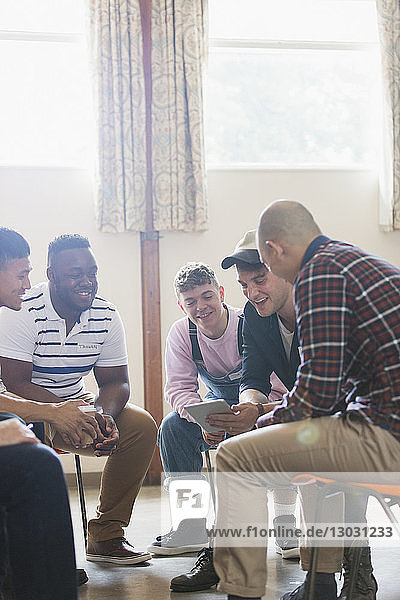 Men with digital tablet talking in group therapy circle