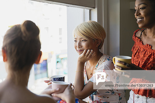 Young women friends drinking coffee at apartment window