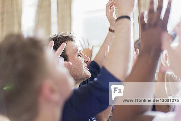 Man praying with eyes closed in prayer group