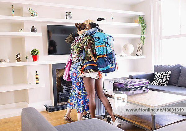 Young women friends hugging  arriving at house rental