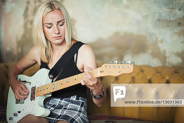 Young woman playing electric guitar on sofa Young woman playing electric guitar on sofa