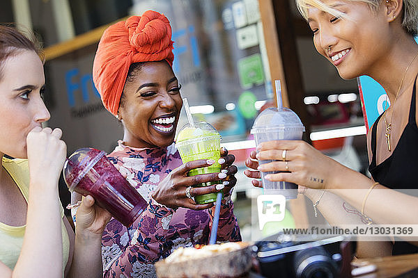 Young women friends drinking smoothies at sidewalk cafe