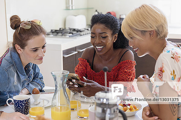 Young women friends enjoying breakfast  using smart phone in kitchen