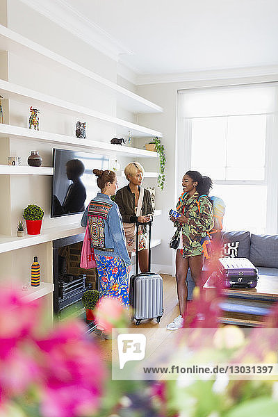 Young women friends with suitcases talking in house rental