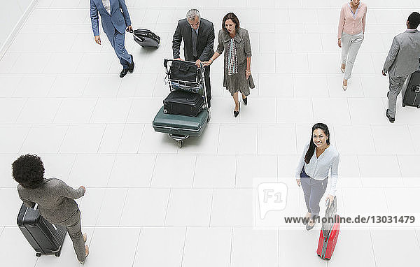 High angle portrait smiling businesswoman with suitcase in airport
