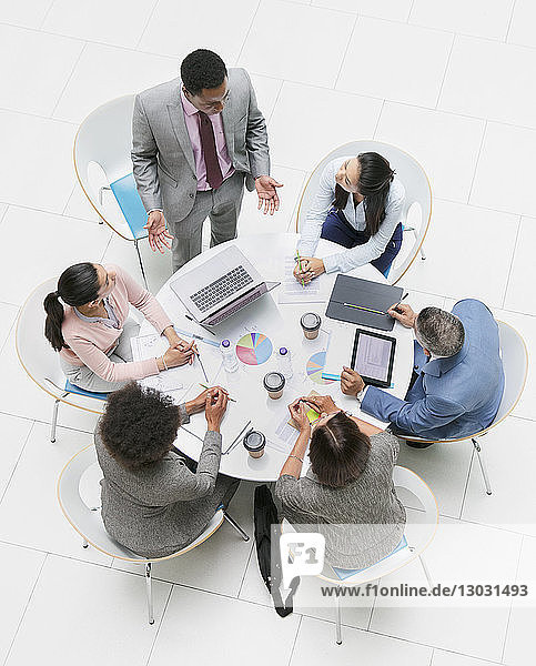 High angle view businessman leading meeting at round table