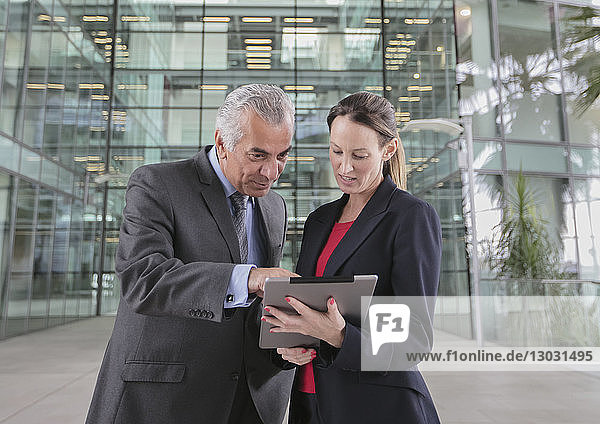 Business people using digital tablet outside modern office building
