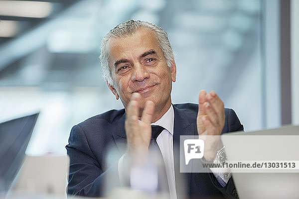 Smiling  confident senior businessman clapping in meeting