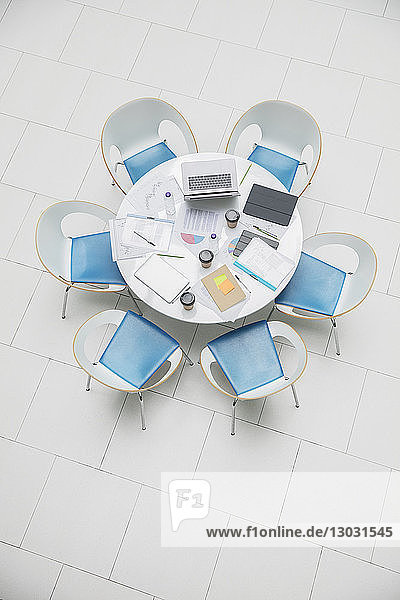 High angle view business laptop and paperwork on round table