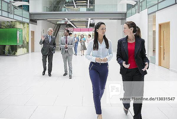 Businesswomen walking and talking in office lobby