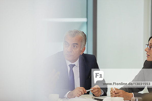 Attentive senior businessman listening in conference room meeting