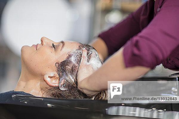 Friseur  der die Haare seiner Kunden im Salon wäscht