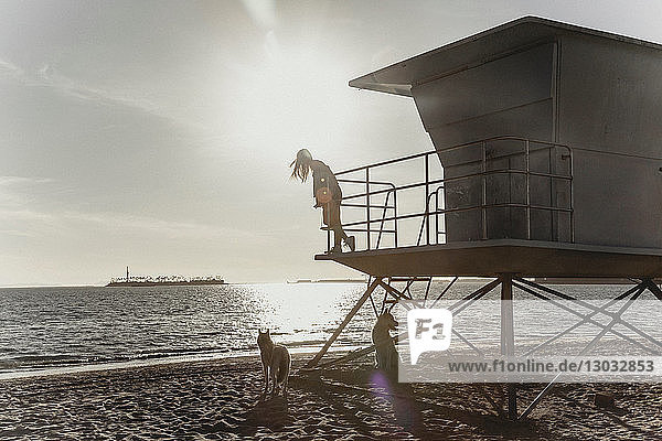 Woman on lifeguard tower  sunset in background