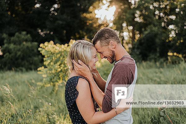 Romantische junge Frau und ihr Freund stehen sich bei Sonnenuntergang im Feld gegenüber