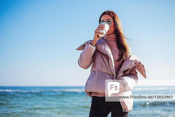 Stylische Frau mittleren Alters am Strand  die Kaffee zum Mitnehmen trinkt  Odessa  Odeska Oblast  Ukraine