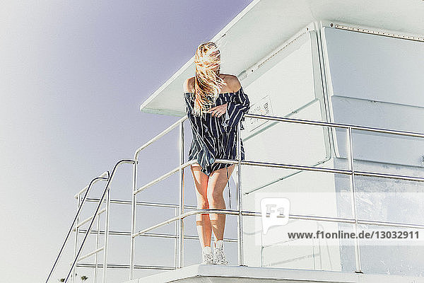 Woman relaxing on lifeguard tower